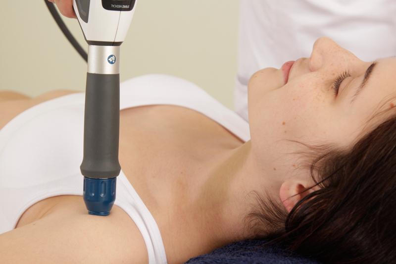 Процедура ударно-волновой терапии на плече.